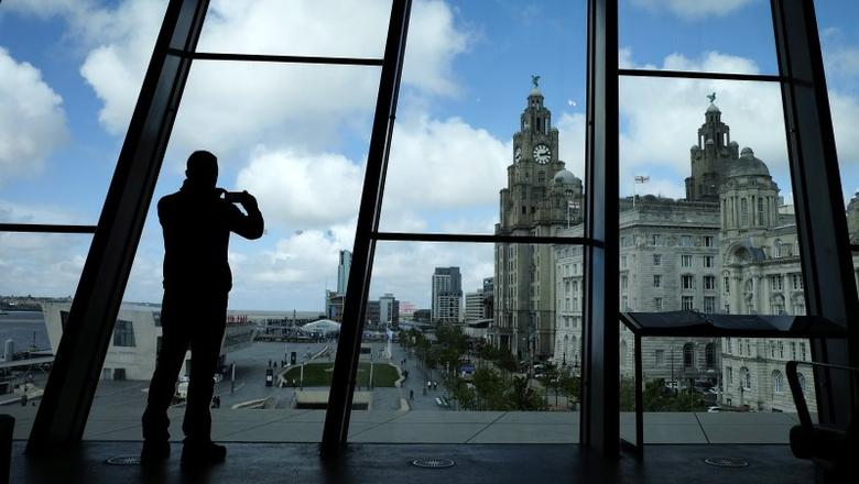A visitor takes a photograph of the Royal Liver Building from a window at the Museum of Liverpool northern England, May 18 , 2016. REUTERS/Phil Noble