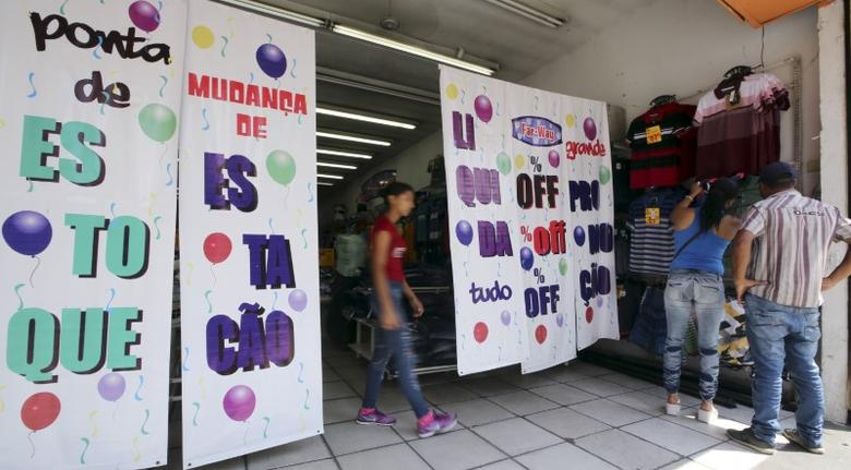 File photo of customers shopping near signs advertising promotional sales at a clothing store in Sao Paulo, Brazil, January 8, 2016.  REUTERS/Paulo Whitaker