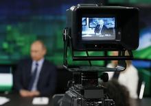 Президент России Владимир Путин в видоискателе телекамеры в студии телеканала Russia Today (RT) в Москве 11 июня 2013 года. Россия в понедельник обвинила Великобританию в политической цензуре, после того как подконтрольный британским властям банк отказал в обслуживании телеканалу RT, созданному Кремлем для вещания на зарубежную аудиторию. Россия в понедельник обвинила Великобританию в политической цензуре, после того как подконтрольный британским властям банк отказал в обслуживании телеканалу RT, созданному Кремлем для вещания на зарубежную аудиторию. REUTERS/Yuri Kochetkov/Pool