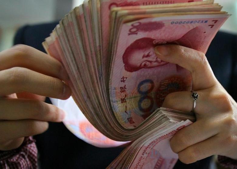 2006年3月6日,南京一家银行的职员在清点人民币纸币。REUTERS/Stringer