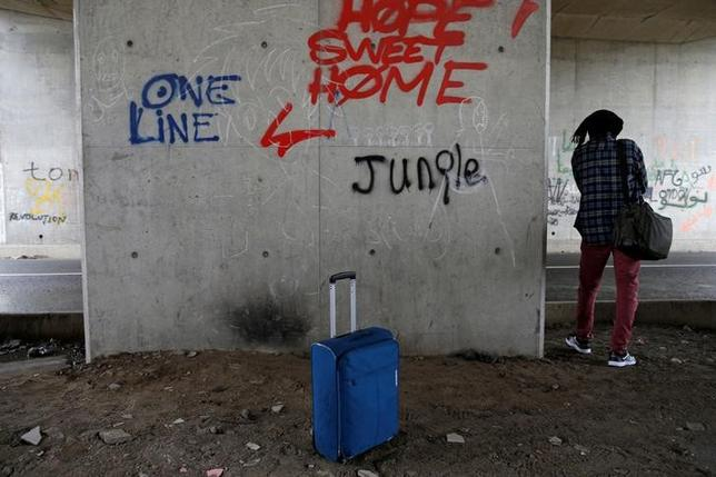 A migrant stands neat a suitcase with his belonging before departing the Calais camp called the ''Jungle'' to take classes at Lille University, in France, October 18, 2016.  REUTERS/Pascal Rossignol