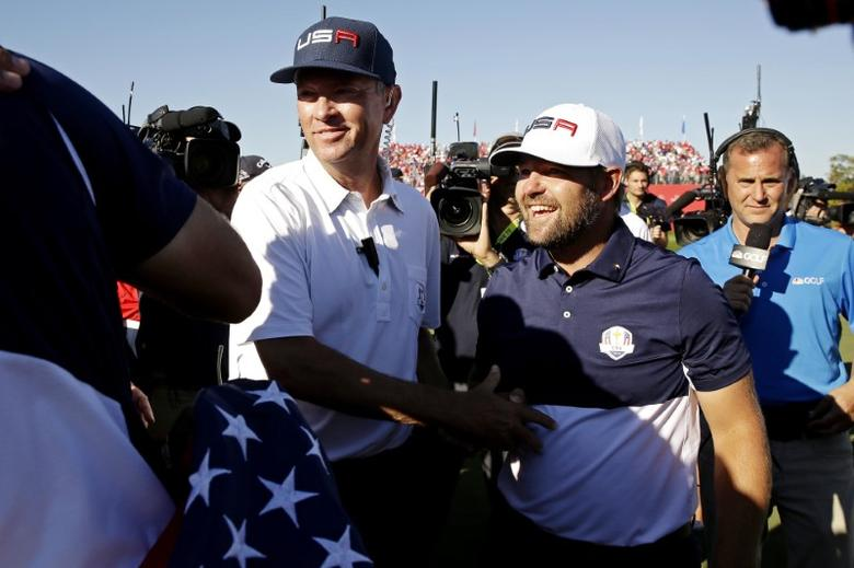 Team USA captain Davis Love III celebrates with  Ryan Moore of the United States after winning the Ryder Cup during the single matches in 41st Ryder Cup at Hazeltine National Golf Club. Mandatory Credit: Rob Schumacher-USA TODAY Sports  / Reuters