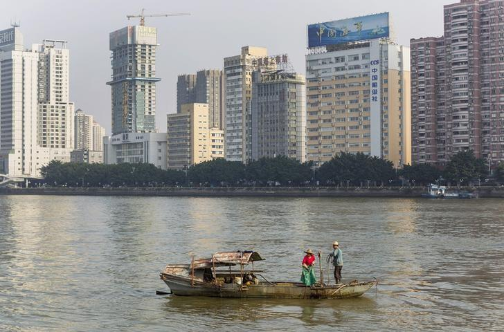 A couple fishing along Pearl River (or Zhu Jiang) next to office buildings in downtown Guangzhou, Guangdong province December 7, 2013.  REUTERS/Stringer