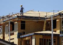 Un trabajador en el techo de una vivienda en Carlsbad, EEUU, sep 22, 2014. Los inicios de construcción de casas en Estados Unidos se desplomaron a su nivel más bajo en un año y medio en septiembre debido a un fuerte declive en la edificación de viviendas multifamiliares, aunque el incremento en el segmento de unidades unifamiliares apuntaba a una fortaleza sostenida en el mercado inmobiliario. REUTERS/Mike Blake