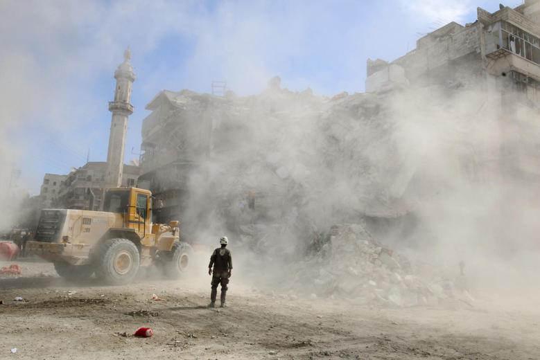 A Civil Defence member stands as a front loader removes debris after an air strike Sunday in the rebel-held besieged al-Qaterji neighbourhood of Aleppo, Syria. REUTERS/Abdalrhman Ismail