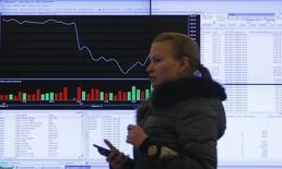 Жещина идет мимо офиса Московской фондовой биржи. Российские фондовые индексы во вторник продолжают слабое повышение в отсутствие выраженной динамики на нефтяном и развивающихся рынках, а котировки угольных компаний корректируются после ралли. REUTERS/Maxim Shemetov (RUSSIA - Tags: BUSINESS POLITICS)