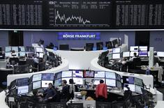 Traders work at their desks in front of the German share price index, DAX board, at the stock exchange in Frankfurt, Germany, October 21, 2016. REUTERS/Staff/Remote