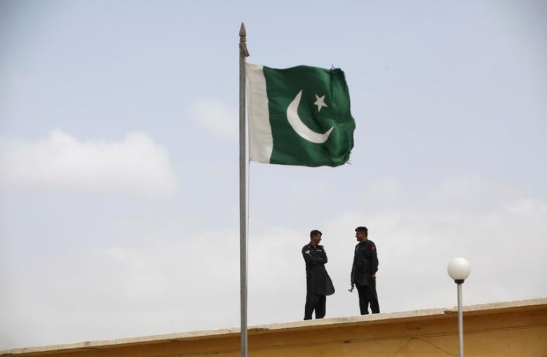 A Pakistani flag flies on a mast as paramilitary Frontier Corps soldiers talk while guarding at Karachi
