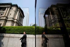 Человек проходит мимо здания Банка Японии в Токио 22 мая 2013 года. Банк Японии воздержался от расширения мер стимулирования во вторник, несмотря на то, что вновь отодвинул сроки достижения целевого уровня инфляции, сигнализировав, что не будет менять политику при отсутствии серьезных потрясений, которые могут поставить под угрозу хрупкое восстановление экономики. REUTERS/Yuya Shino/File Photo