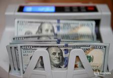 Машинка для счета денег пересчитыывает 100-долларовые банкноты. Доллар, скорее всего, подорожает в течение ближайшего года, поскольку ФРС проводит политику неизбежного, но постепенного повышения ставок, сказали аналитики валютного рынка, опрошенные Рейтер.  REUTERS/Valentyn Ogirenko