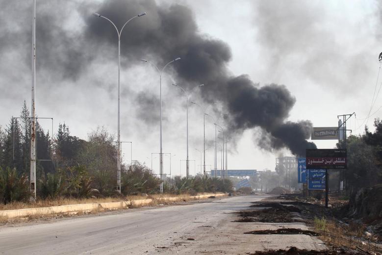 Smoke rises near a damaged road in Dahiyet al-Assad, west Aleppo city, Syria