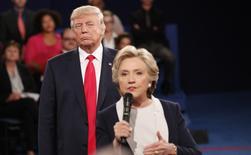 La incertidumbre sobre el resultado de las elecciones en Estados Unidos pasó el miércoles factura al principal índice de la bolsa española, que encarriló su tercera jornada de caídas y perdió la cota de los 9.000 puntos. En la imagen, el candidato republicano a la Casa Blanca, Donald Trump, escucha a su oponente demócrata Hillary Clinton, durante un debate en San Luis, Misuri, el 9 de octubre de 2016.  REUTERS/Rick Wilking