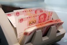 """En la imagen de archivo, una máquina cuenta billetes de 100 yuanes chinos en la filial de un banco comercial en Pekín. 30 de marzo de 2016. China cubrirá las necesidades """"razonables"""" de financiación de los gobiernos locales y frenará la recaudación ilegal de fondos, dijo el viernes el Ministerio de Finanzas. REUTERS/Kim Kyung-Hoon"""