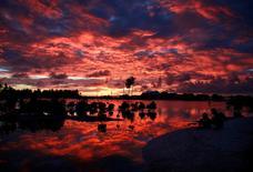 En la imagen de archivo, habitantes del pueblo de Tangintebu en la isla de Kiribati en el Pacífico central, el 25 de mayo de 2013. Grandes petroleras, como Saudi Aramco, Royal Dutch Shell y Total, prometieron el viernes invertir 1.000 millones de dólares en tecnologías para reducir la emisión de dióxido de carbono y ayudar a combatir el cambio climático. REUTERS/David Gray