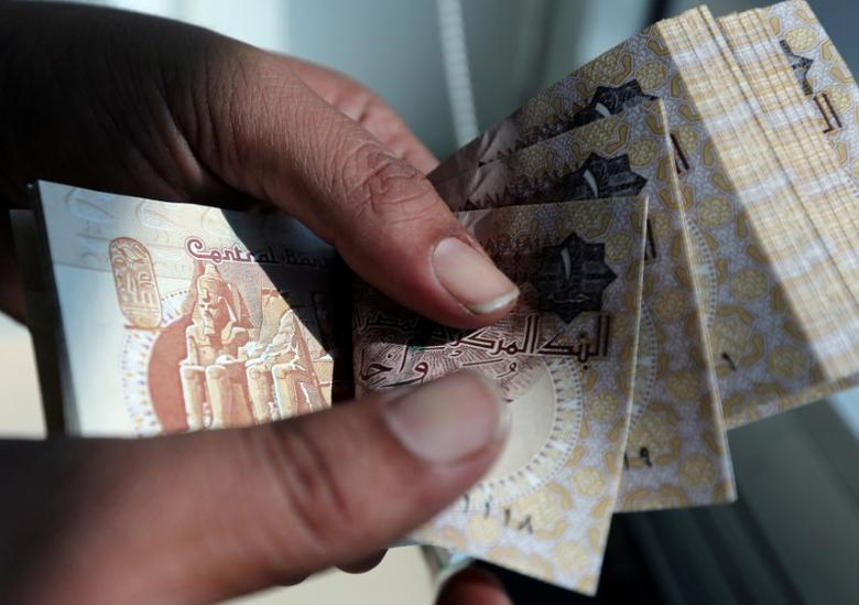 A man counts Egyptian pounds outside a bank in Cairo, Egypt October 24, 2016.  REUTERS/Mohamed Abd El Ghany/File Photo