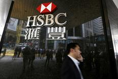 Un hombre camina frente al logo de HSBC en las afueras del distrito financiero de Hong Kong, China  2 de Junio, 2015.  HSBC reportó una caída de un 86 por ciento en sus ganancias antes de impuestos del tercer trimestre, tras sufrir un impacto negativo en sus resultados de 1.700 millones de dólares por la venta de su unidad brasileña y unos movimiento cambiarios adversos.  REUTERS/Bobby Yip/File Photo