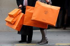 Las ventas minoristas en los 19 países que comparten el euro cayeron un 0,2 por ciento en septiembre respecto a agosto, dijo el lunes Eurostat, la oficina de estadística de la Unión Europea. En la imagen de archivo, una pareja pasea con bolsas de la tienda de Hermes en París el 21 de marzo de 2013. REUTERS/Philippe Wojazer/