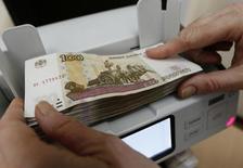 Кассир пересчитывает 100-рублевые банкноты. Рубль был в целом стабилен на торгах понедельника на фоне глобального спроса на риск сокращая потери от утреннего падения к доллару, укрепившегося после воскресного решения ФБР не возбуждать уголовное дело против претендующей на пост президента США Хиллари Клинтон. REUTERS/Ilya Naymushin