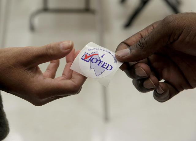 A poll worker hands out an ''I voted'' sticker to a voter during the U.S. presidential election at Potomac Middle School in Dumfries, Virginia, U.S., November 8, 2016.      REUTERS/Joshua Roberts