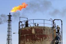 Рабочие на НПЗ Al-Shu'aeba в Басре 27 сентября 2005 года. Мировой спрос на нефть из стран-членов ОПЕК вырастет в ближайшие три года, говорится в ежегодном прогнозе картеля, а это может означать, что решение организации допустить обвал цен на сырьё в 2014 году ради сокращения поставок из стран с более высокой себестоимостью добычи, включая сланцевую нефть из США, оправдывает себя, так как доля картеля на рынке будет расти.  REUTERS/Atef Hassan