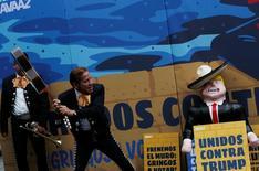 Мексиканский музыкант замахивается на портрет кандидата в президенты США от республиканцев Дональда Трампа в Мехико 25 сентября 2016 года. Национальная валюта Мексики резко подешевела во вторник, после того как данные о результатах голосования в половине с лишним штатов США, в том числе ключевой Флориде, усилили позиции кандидата в президенты от республиканцев Дональда Трампа. REUTERS/Carlos Jasso