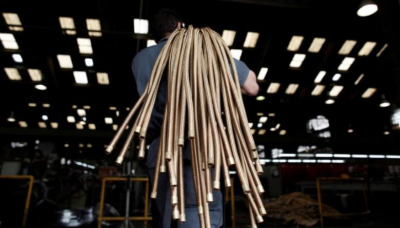 An employee carries copper hoses at the Sociedade Paulista de Tubos Flexiveis (SPTF) metallurgical company which manufactures flexible metal hoses, in Sao Paulo April 20, 2012.  REUTERS/Nacho Doce/File Photo