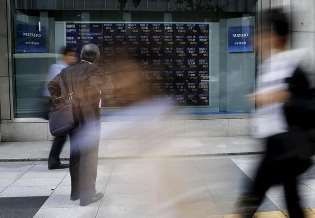 11月15日、東京株式市場で日経平均は4日ぶりの小反落。一時1ドル108円台半ばまでドル高/円安方向に振れた為替が支援材料となり、序盤は買いが優勢の展開。取引時間中としては2月2日以来、約9カ月半ぶりに1万7700円台を回復した。写真は株価ボードを眺める通行人。都内で昨年10月撮影(2016年 ロイター/Toru Hanai)