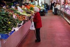 Los precios siguieron recuperando terreno en octubre, creciendo a una tasa no vista desde agosto de 2013 tras volver a terreno positivo el mes anterior por primera vez en un año, mostraron el martes datos definitivos del INE.    En la imagen, una mujer en un puesto de fruta y verdura en Madrid el 29 de enero de 2013. REUTERS/Juan Medina