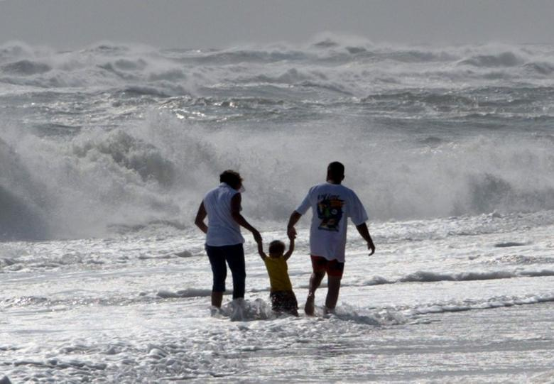 Parents carry their young son over surging waves on the Outer Banks of North Carolina, September 16, 2003. REUTERS/Jason Reed