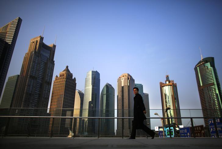 图为2014年3月11日资料图片,显示一名男子走在上海浦东金融区。REUTERS/Carlos Barria