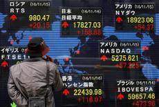 Los bonos globales se encaminan a su mayor caída quincenal en décadas porque las expectativas de una inflación al alza reducen la demanda por los activos de interés fijo. Imagen de un hombre mirando pantallas con cotizaciones ante una casa de valores en Tokio, el 16 de noviembre de 2016. REUTERS/Toru Hanai