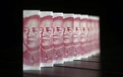 Chinese 100 yuan banknotes are seen in this picture illustration taken in Beijing July 11, 2013. China's central bank has standardised rules on cross-border yuan transactions for domestic banks and companies, the latest step to boost the yuan's global influence. REUTERS/Jason Lee (CHINA - Tags: BUSINESS) - RTX11JG1