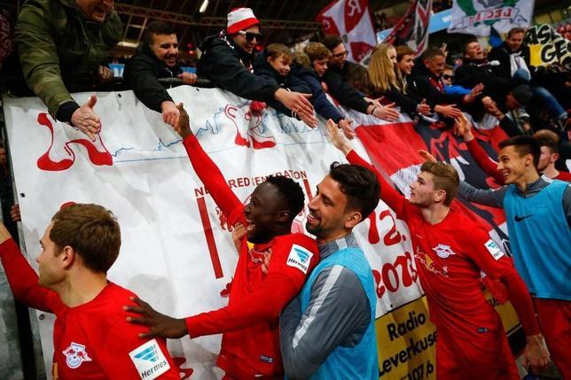 11月18日、サッカーのドイツ1部ブンデスリーガ、今季昇格のライプチヒがレーバークーゼンを3─2で下し、暫定首位に浮上した。写真はサポーターと勝利を喜ぶライプチヒの選手たち(2016年 ロイター/Wolfgang Rattay)
