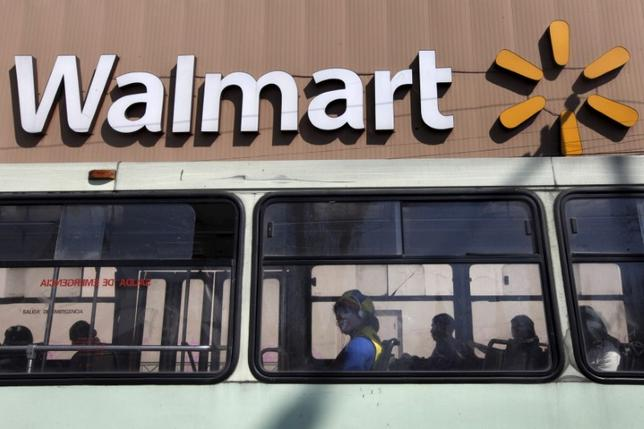 A clown sits inside a bus seen in front of a Wal-Mart store in Mexico City January 11, 2013.  REUTERS/Edgard Garrido/File Photo