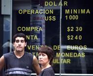 Peatón parado junto a una tabla electrónica que muestra el valor de intercambio del peso argentino con el dólar. Las monedas latinoamericanas continuarían sujetas a pérdidas esta semana, incluso a pesar de que las autoridades de México y Brasil comenzaron a actuar para moderar la corriente de bajas que desató la elección de Donald Trump como presidente de Estados Unidos.REUTERS/Enrique Marcarian  EM/MMR - RTR2ILG