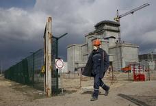 Рабочий идет по территории АЭС в Чернобыле на фоне хранилища радиоактивных отходов 21 апреля 2015 года. Две китайские компании планируют построить солнечную электростанцию в зоне отчуждения вокруг Чернобыльской АЭС - территории, закрытой для свободного доступа из-за радиационного заражения после аварии в 1986 году. REUTERS/Valentyn Ogirenko