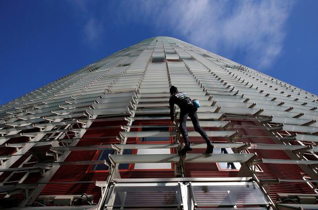 11月25日、世界各地の高層建築に命綱なしで登ることから「スパイダーマン」の異名を取るフランス人、アラン・ロベール氏(54)が、バルセロナで最高層のビルの1つであるトーレ・アグバルに上った(2016年 ロイター/Albert Gea)