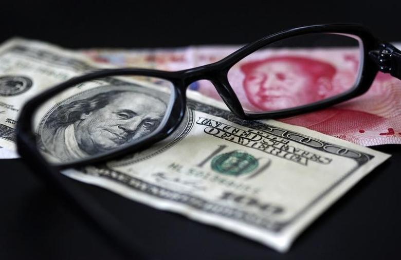 2010年10月13日,图为透过镜片看到的美元和人民币纸币。REUTERS/Nicky Loh