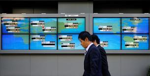 Hombres caminan frente a unas pantallas que muestra el índice Nikkei y otras divisas afuera de una correduría en Tokio, Japón. 6 de julio de 2016   REUTERS/Toru Hanai