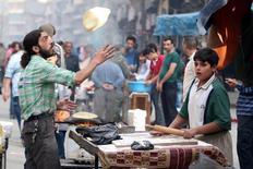 Мужчина готовит хлеб в контролируемом повстанцами районе Алеппо. 25 октября 2016 года. Россия в ближайшее время поставит в Сирию пшеницу в качестве гуманитарной помощи, сказал журналистам вице-премьер РФ Аркадий Дворкович. REUTERS/Abdalrhman Ismail