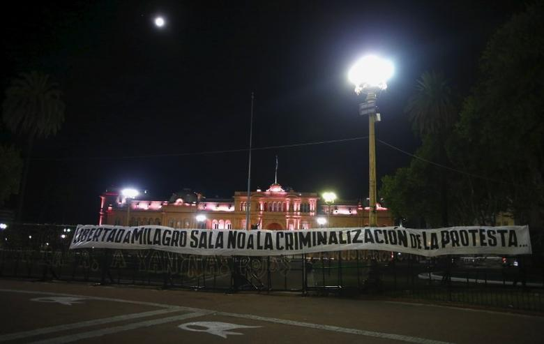 A banner that reads  ''Freedom for Milagros Sala'', '' No to criminalization of the protest'' hangs on fence near the Argentina's Government House (back) in Buenos Aires, January 28, 2016. REUTERS/Enrique Marcarian