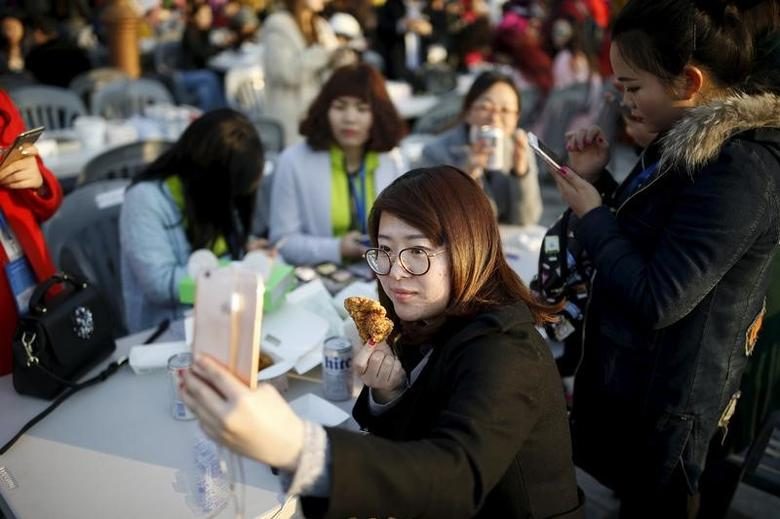 A Chinese tourist takes a selfie with a piece of fried chicken during an event organized by a Chinese company at a park in Incheon, South Korea, March 28, 2016. REUTERS/Kim Hong-Ji