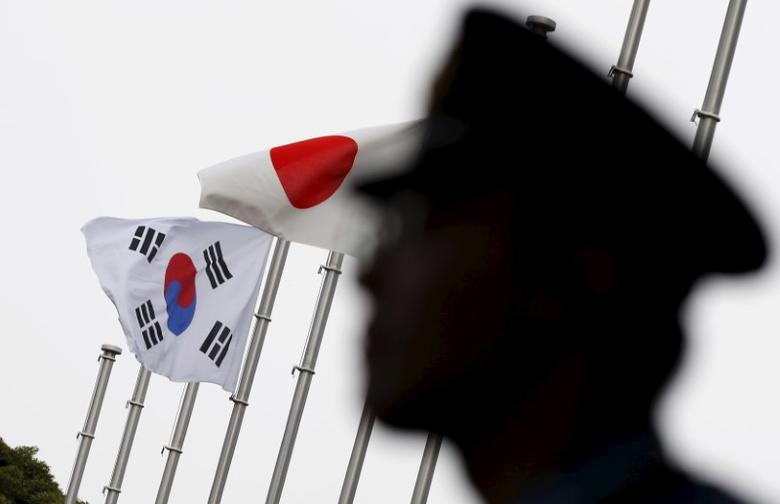 A police officer stands guard near Japan and South Korea national flags at a hotel, in Tokyo  June 22, 2015. REUTERS/Toru Hanai