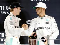 Formula One - F1 - Abu Dhabi Grand Prix - Yas Marina Circuit, Abu Dhabi, United Arab Emirates - 27/11/2016 - Mercedes' Formula One driver Nico Rosberg (L) of Germany shakes hands with Lewis Hamilton of Britain. REUTERS/Ahmed Jadallah