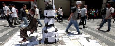 Una persona promocionando empleos en una calle en Sao Paulo, nov 19, 2014. La economía de Brasil se hundió más profundamente en recesión durante el tercer trimestre, contra las expectativas que tenía el Gobierno de que un alza en la confianza del consumidor y de las empresas generara un repunte tras la destitución de la ex presidenta Dilma Rousseff.  REUTERS/Paulo Whitaker