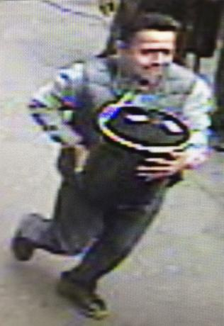 An unidentified man is shown in this still image from surveillance video carrying a 86-pound pail of gold flakes valued at $1.6 million off an armored truck two months ago in Manhattan provided by the New York Police Department  in New York, November 30, 2016.   Courtesy of NYPD/Handout via REUTERS
