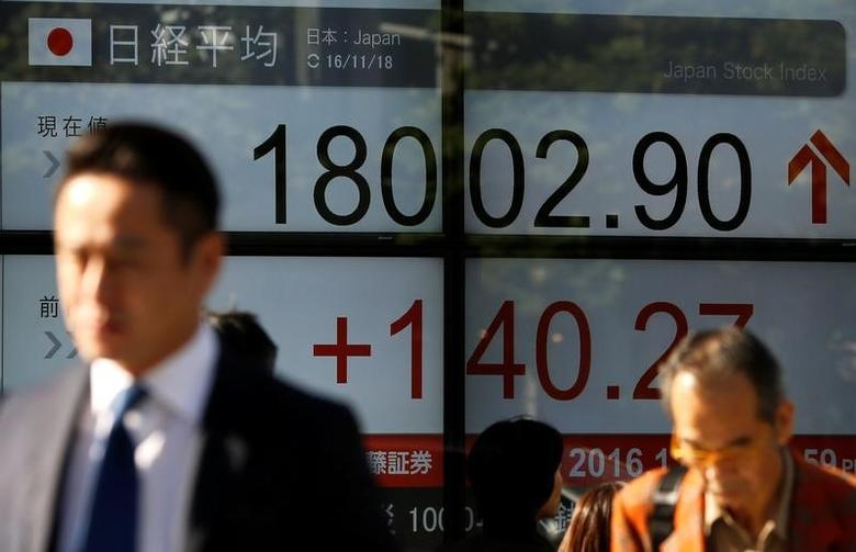 People walk past an electronic board showing Japan's Nikkei average outside a brokerage in Tokyo, Japan, November 18, 2016.   REUTERS/Toru Hanai