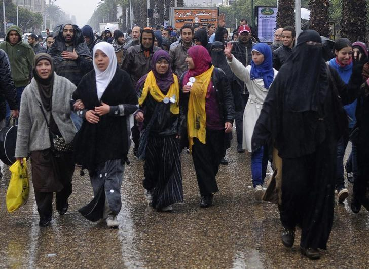 Supporters of the Muslim Brotherhood and ousted Egyptian President Mohamed Mursi walk in the rain during a protest at Al-Haram street, in Cairo December 13, 2013. REUTERS/Stringer/Files