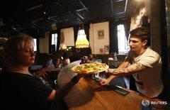 Сотрудники ресторана держат в руках пиццу в Москве 10 ноября 2014 года. Деловая активность в российском секторе услуг в ноябре 2016 года оставалась в зоне роста десятый месяц подряд, и темпы ускорения оказались максимальными за последние четыре месяца, свидетельствует опрос, проведенный компанией Markit.     REUTERS/Maxim Zmeyev