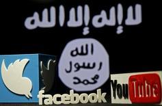 Photo de Twitter, Facebook and Youtube logos devant un drapeau de l'EI. YouTube, Facebook, Twitter et Microsoft ont annoncé mardi leur volonté de redoubler d'efforts pour supprimer les contenus extrémistes de leurs sites en créant une base de données commune. /Photo d'archives/REUTERS/Dado Ruvic